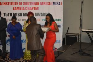 PSAf Executive Director Ms. Lilian Saka-Kiefer (in red dress) presenting an award to Sylivester Mwale during the 2017 MISA Media Awards in Lusaka